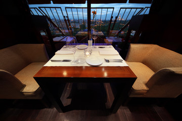 serving at table with tablecloth and seats in empty restaurant