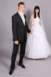 Beautiful bride and groom hold hands and stand in studio on gray
