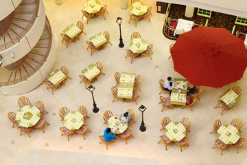 People breakfast in hotel restaurant; top view; spiral staircase