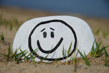 smiley sketch on a stone on the sand