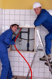 Plumbers working in a tiled room