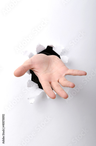Hand through the hole in paper