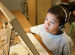 LIttle Boy with Headphones Concentrating at the Computer