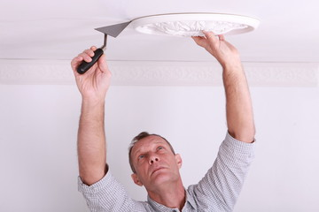 Plasterer working on ceiling motif