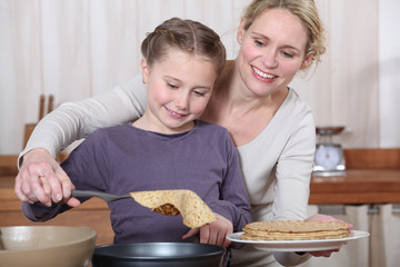 Mother and daughter making crepes together