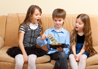 boy shows a wallet of dollars to two impressed girls