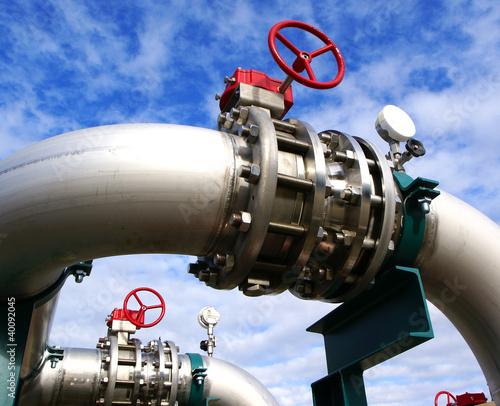 Leinwanddruck Bild Industrial zone, Steel pipelines and valves against blue sky