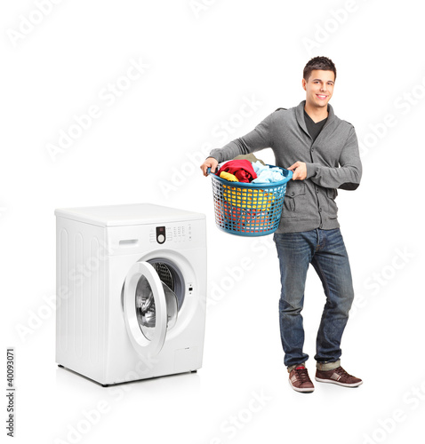 Man with laundry basket posing next to a washing machine