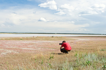 Video operator works on the bank of salty lake