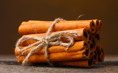 Cinnamon sticks on wooden table on brown background