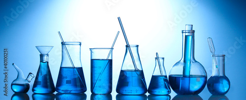 Test-tubes with blue liquid on blue background