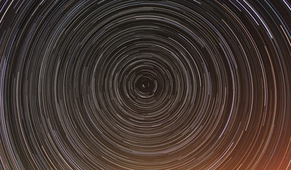 Cumulative time lapse of star trails in night sky.