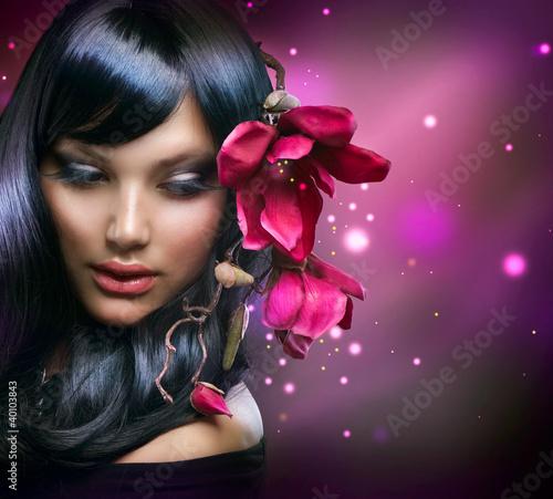 Mode-Brunette-Mädchen mit Magnolien-Blumen