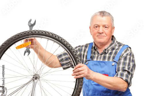 Middle aged man holding wrench and repairing bicycle wheel