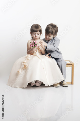 Two beautiful boys and girls in wedding dresses