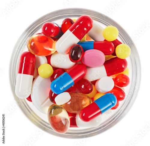 Pills, tablets and drugs heap in glass bowl isolated on white