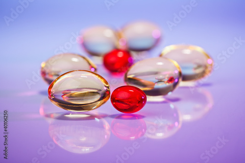 Pills (capsules) of cod-liver oil on violet, macro view with sel