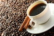 A cup of coffee and cinnamon sticks on coffee beans, closeup