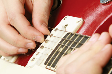 Close-up of a guitar and playing hands