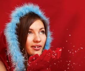 Happy beautiful woman blowing snowflakes in winter season