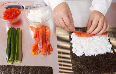 cook making   sushi rolls  with salmon