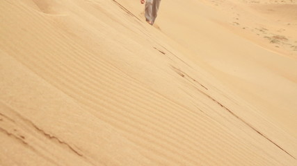 Exhausted businessman climbing up dune in the desert