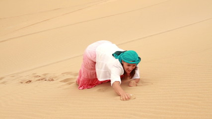 Exhausted woman climbing up dune in the desert