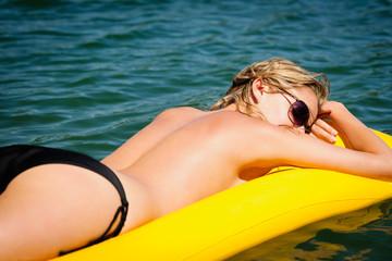 Summer woman sunbathe on water floating mattress