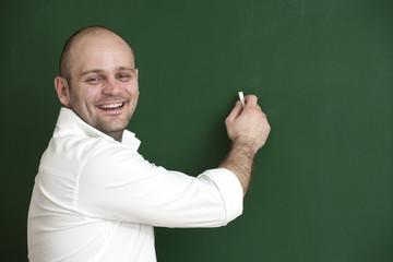 Lächelnder Lehrer schreibt an die Tafel.