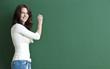 Lächelnde Lehrerin steht an die Tafel.