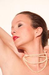 Joven posando con collar de perlas