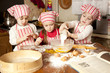 Three little chefs enjoying in the kitchen making big mess. Litt