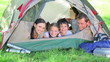 Smiling family lying in a tent