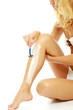 A woman is shaving her leg on white background