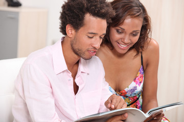 Young couple browsing through magazine
