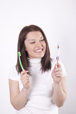 Young beautiful woman deciding which toothbrush to use