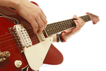 Close-up of a guitar and playing hands, isolated on white