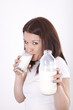 Young beautiful woman drinking milk from glass
