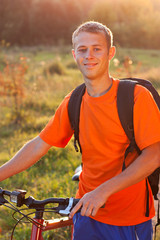 Happy man cyclist illuminated by sunlight