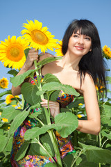 Young woman in the field of sunflowers