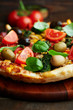 Pizza with olives, tomatoes and spinach