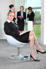 Businesswoman sat in chair with colleagues in background