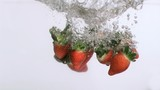 Strawberries in super slow motion falling in the water