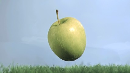 Green apple in super slow motion falling on the grass