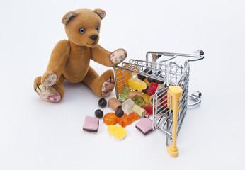 игрушечный мишка и гора сладостей