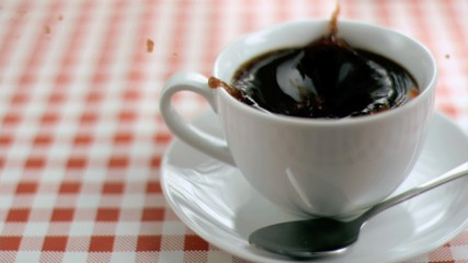 Sugar in super slow motion falling in a cup of coffee