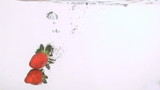Strawberries falling in super slow motion in the water