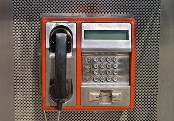 Orange public telephone on metallic background