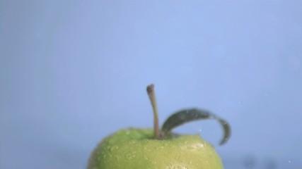 Rain in super slow motion falling on a green apple