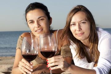 Zwei Frauen am Strand trinken Wein